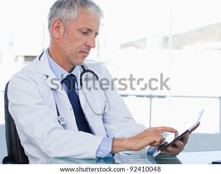 Serious doctor working with a tablet computer in his office