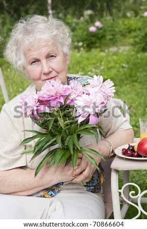Serious elderly woman sitting in the garden with a bouquet of pink flowers