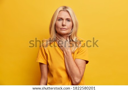 Serious elderly woman suffers sore throat touches neck and grimaces from pain feels unwell while swallowing dressed in casual clothes poses against yellow background. Influenza health problems Сток-фото ©
