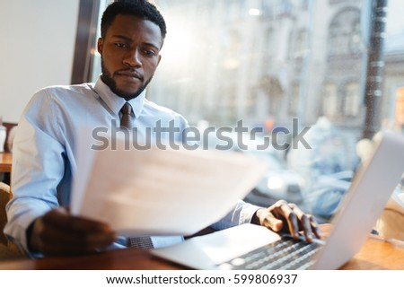 Serious employer reading resumes of candidates for vacancy