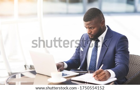 Serious Entrepreneur Using Laptop And Taking Notes Working In Outdoor Cafe In City. Business During Coronacrisis. Stock photo ©