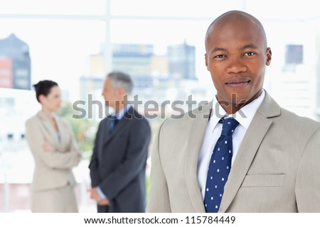 Serious executive in a suit standing upright while his team is behind him