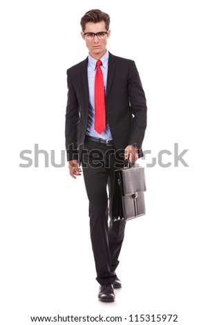 serious fashion business man wearing glasses and holding a briefcase, walwing forward
