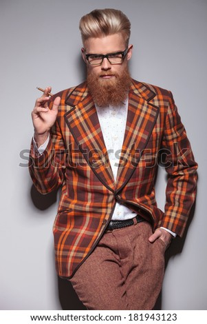 serious fashion man with beard and nice hairstyle smoking a cigarette and looks at the camera