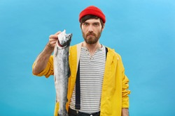 Serious fashoinable man with beard dressed in yellow raincoat and red hat holding big fish in hands. Handsome fisherman showing his huge catch during his vacations isolated over blue background