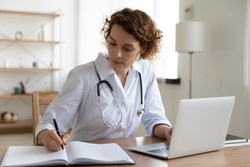 Serious female doctor using laptop and writing notes in medical journal sitting at desk. Young woman professional medic physician wearing white coat and stethoscope working on computer at workplace.