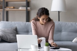 Serious female in glasses paying utility bills, taxes, rental fees use online services e-bank app on laptop. Young woman work from home sit on couch hold paper invoice calculate expenses, make report