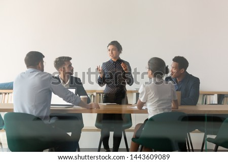 Serious female indian manager talk at diverse group meeting consult clients in boardroom behind glass door, multicultural business people with woman team leader discuss work at corporate briefing