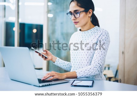 Serious female manager making online payment via laptop computer holding telephone for confirming banking operation, receptionist booking service on netbook using cellular for messaging at desk #1055356379