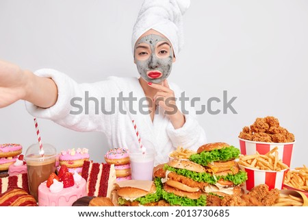 Serious female model with beauty cay mask on face wears red lipstick makes selfie against white background stands near table full of delicious treats wears bathrobe towel on head. Excess of calories Photo stock ©