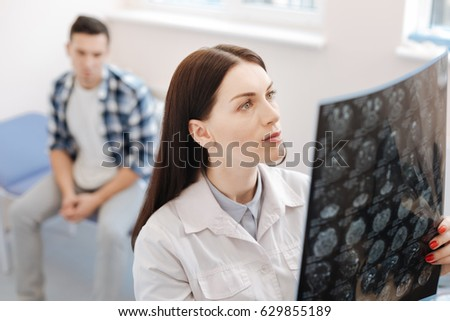 Serious female neurologist examining the X ray photo