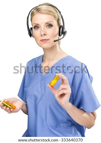 Serious female nurse with light blond hair in uniform talking on headset and holding pills - Isolated