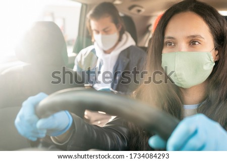 Serious female taxi driver in protective mask and gloves holding by steer while driving to client address during period of epidemy