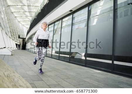Serious fit old lady running along modern city building #658771300