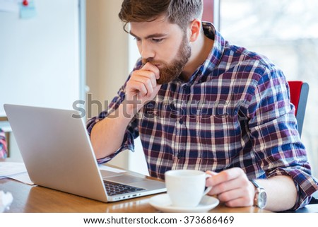 Serious focused bearded young man in checkered shirt sitting at the table and using laptop