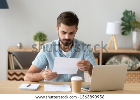 Serious focused businessman, freelancer attentively reading paper document, unpleasant news, received letter, analyzing offer, financial report with project statistics, notification