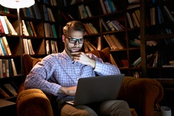 Serious focused busy young business man student using laptop computer working or studying late e learning online sitting in chair watching webinar at home office with bookcase in night lamp light.