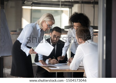 Serious focused multi-ethnic team working together do paperwork lawyer and command reviewing contract details, financiers analyzing financial statistics work results, teamwork group meeting concept