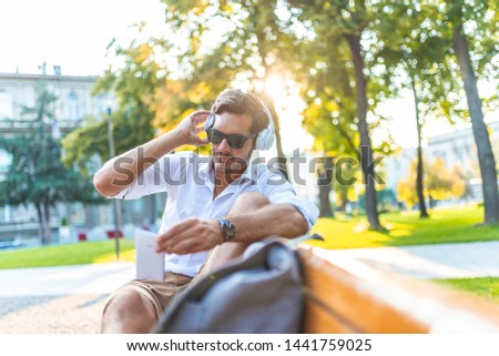 Serious focused student typing message on smartphone in park. Handsome young man in shirt with backpack sitting on bench outdoors and using mobile phone. Digital device concept #1441759025