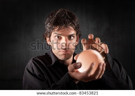 Serious fortune teller holds crystal ball over maroon background