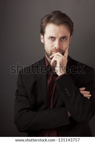 Serious forty years old businessman standing on a grey background