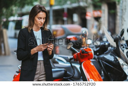 serious girl in black jacket uses an app in smartphone to rent and pay for moped planning walking on city outdoors, business woman looks at screen of her mobile phone and plans ride on scooter on map ストックフォト ©