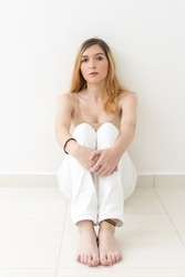 Serious girl is sitting on the floor with her hands on her knee. She does not wear shoes, she is barefoot. White and empty room.