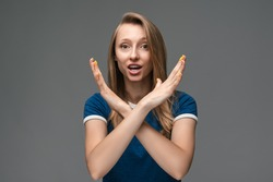 Serious girl with blonde straight hair in blue t shirt doing stop sign with crossed hands, gesturing stop, finish, showing symbol of rejection, body language. Studio shot, gray background