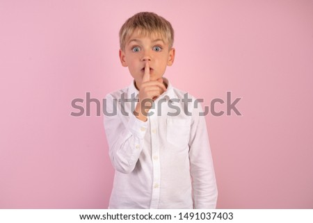 Serious good looking young boy with trendy hairdo, keeps fore finger on lips, tries to keep conspiracy, looks aside, says: Sh, make silence please. Isolated shot of attractive child shows silence sign
