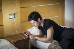 Serious Gorgeous Young Man Connect his Mobile Phone to a Charger While Lying on his Side on the Bed.