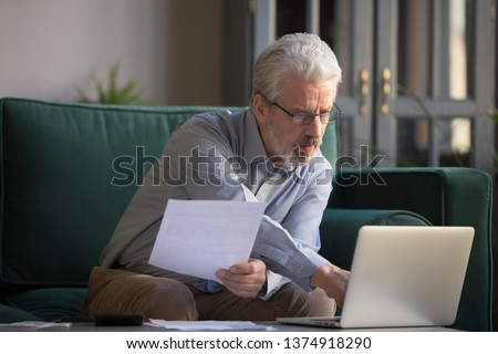 Serious grey haired mature man in glasses calculating bills, using laptop, online bank service at home, focused middle aged grandfather looking at computer screen, typing, checking loan documents Сток-фото ©