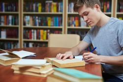 Serious guy rewriting information from book into his copybook