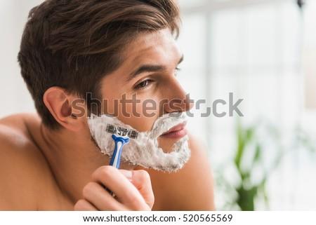 Serious guy shaving his beard