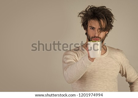 serious guy with tea cup on grey background. Morning with coffee or milk. Cold and flu, single. Insomnia, refreshment and energy. Man with disheveled hair drink mulled wine, copy space