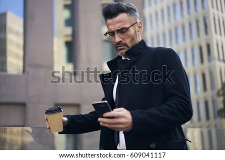 Serious handsome businessman dressed in corporate clothing concentrated checking mail on mobile phone via 4G internet connection holding urban coffee in hand during break standing near office building