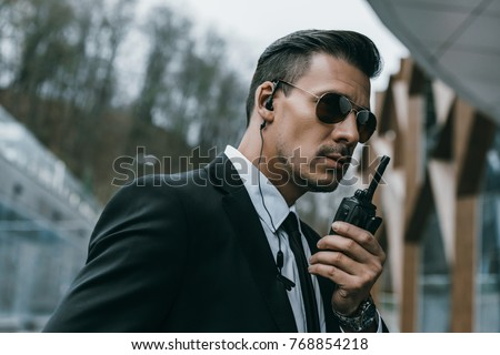 serious handsome security guard talking by portable radio