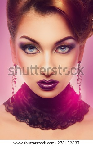 Serious high society person looking at camera with color make up