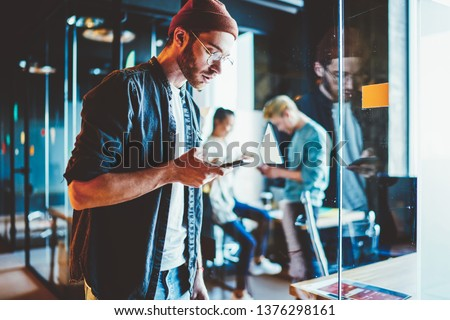 Serious hipster guy in casual wear sending text messages via mobile phone spending time in office, skilled male employee checking mail on smartphone  standing at coworking space during job process #1376298161