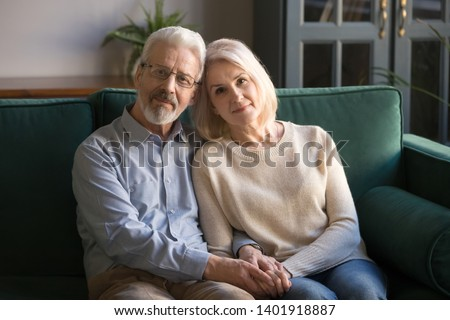 Serious hoary couple of retirees hugging holds hands symbol of devotion and care, spouses sitting on sofa look at camera, forever love, medical insurance, nursing home, services for old people concept