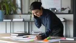 Serious Indian businesswoman talking on cellphone, writing notes on colorful sticky papers in office, employee checking financial documents, working with statistics, consulting client by phone call