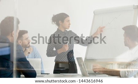Serious indian female business coach manager presenter give presentation point on flip chart explain work result training diverse team workers group in office behind glass door at corporate workshop