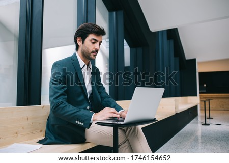 Serious Indian man working with information database on modern laptop computer connecting to internet in workspace, formally dressed male trader downloading financial documents for editing