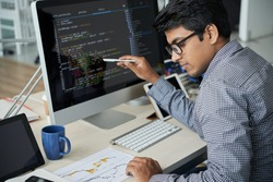 Serious Indian programmer in eyeglasses pointing at computer monitor and checking the statistics of website in document while working at office
