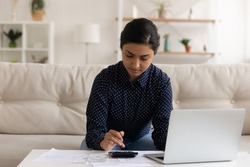 Serious Indian woman calculating expenses, using laptop, sitting on couch at home, focused young female using laptop and calculator, managing planning household budget, preparing financial report