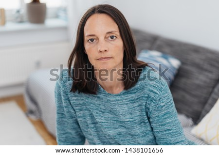 Serious intense mature woman staring at the camera with a deadpan expression as she sits on a sofa at home Stockfoto ©