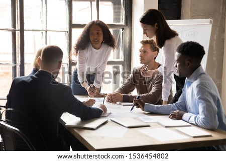 Serious international diverse business team people and african female leader boss discuss financial result review paperwork share ideas brainstorm collaborate work in teamwork at group briefing table