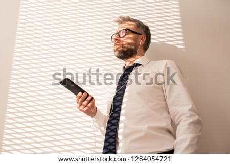 Serious introspective handsome bearded businessman in glasses standing at wall and looking into distance while listening to music on phone