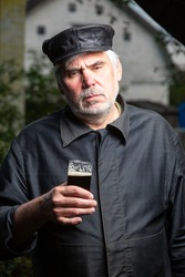 Serious kind sad elderly man with black old-fashioned old clothes and a leather cap with a glass of beer in his hand. Looks at the camera. Vertical orientation.