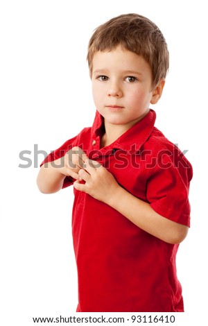 Serious little boy buttoning on a red shirt, isolated on white