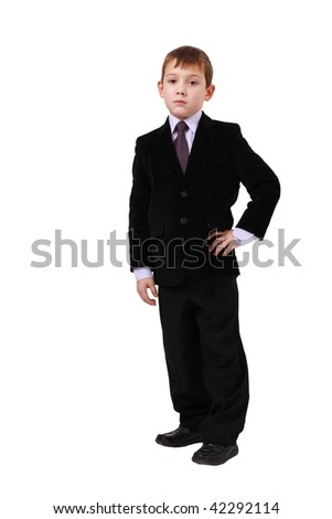 Serious little boy in suit standing on white background
